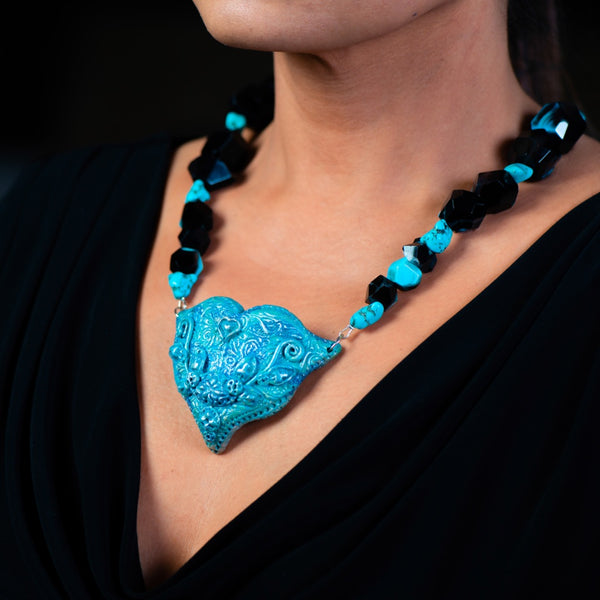 Fashion statement necklace made of clay, turquoise and dragons vein agate with a heart shaped blue pendant.