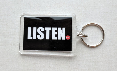"Black keychain reading ""Listen"" in white letters, followed by a smaller KDHX logo."