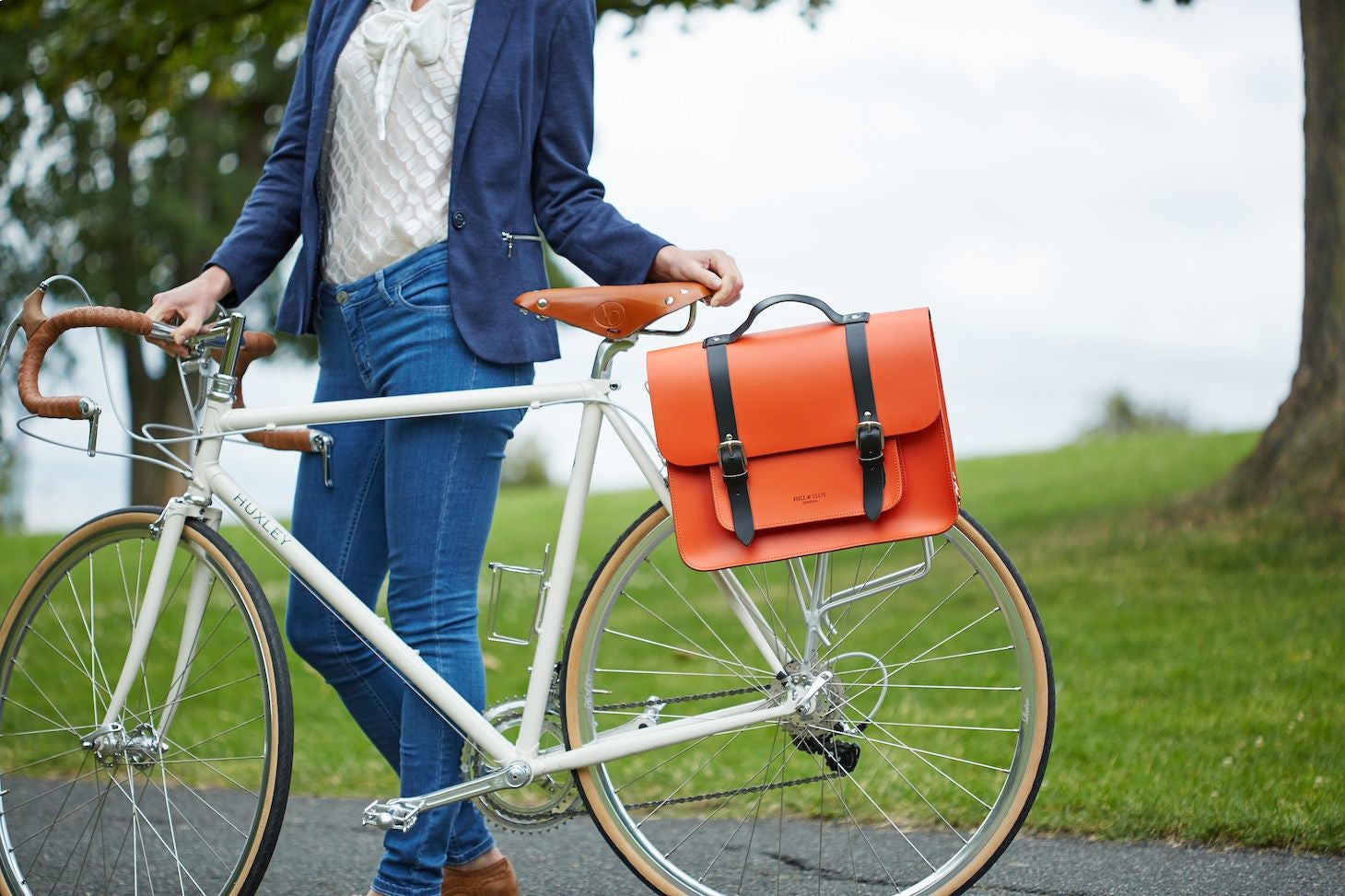 Hill and Ellis Jasper Dutch Orange Leather Pannier on a bike with model in jeans standing near