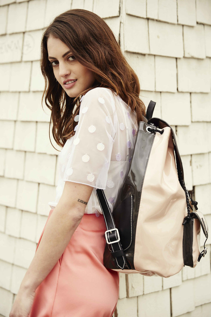 california model with pink backpack with gray sides and black leather.
