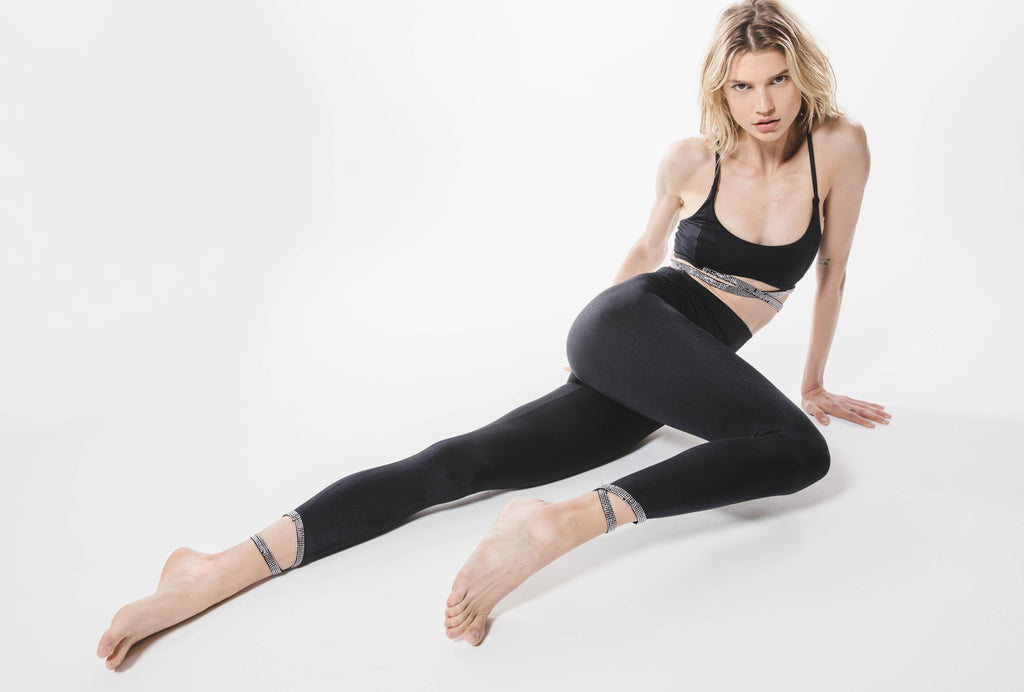 Model sitting in Criss Cross Sport Bra and active legging in color black. Top and legging have rhinestone details.