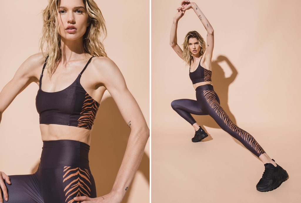 Model stretching in Black Sports Bra and Black Active legging with tiger stripe details down the side.