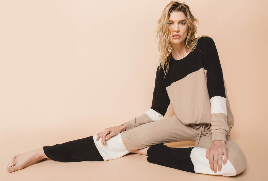 Model sitting in colorblock lounge sweater top and wide leg pant. Colors are tan, white, and black.