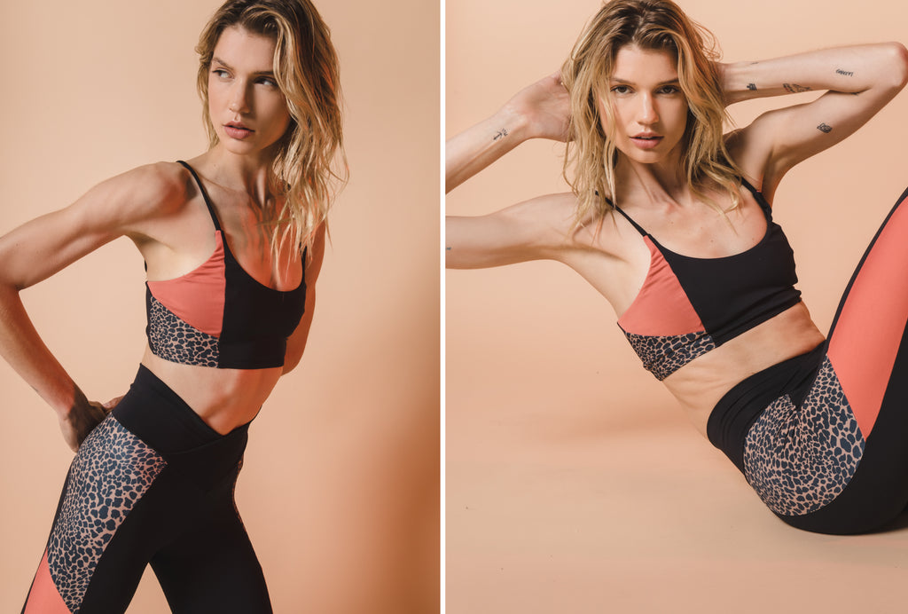 Model stretching and crunching in Colorblock Ivy Sports Bra and Tori active legging in black,coral, and leopard print.