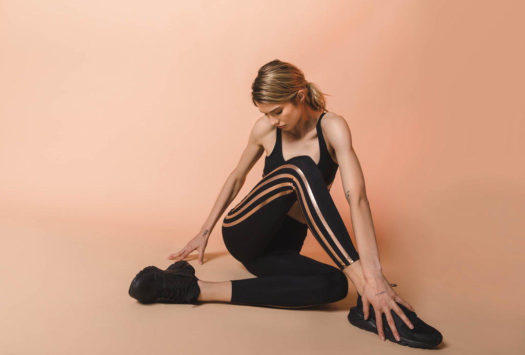 Model sitting and stretching in Leah sport bra top and Jade active legging in black with metallic rose gold stripes.