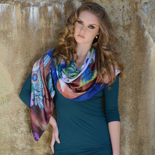 Model wearing Chetna Singh bold jewel tone bird and floral print long silk scarf.