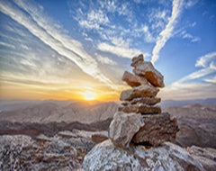 Some stones stacked up on a mountain with a sunset in the background photo
