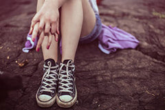 Photo of a young girls legs and sneakers