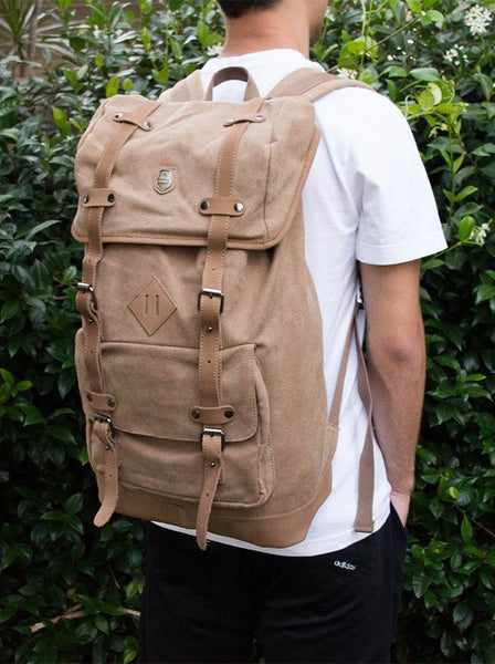 Side view of the light brown canvas daypack worn by stylish man