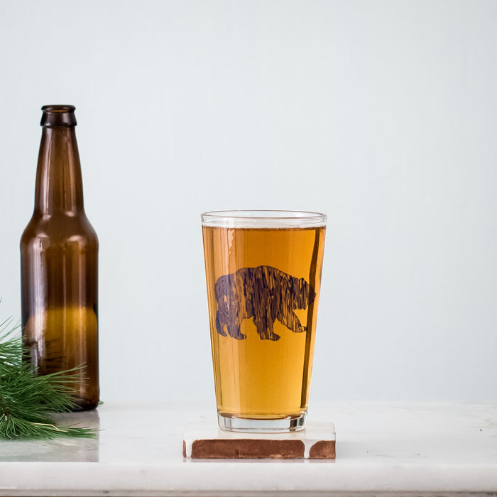 Navy wood grain bear silhouette screen printed on a 16 oz. pint glass