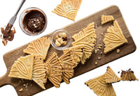 Deliciously looking ferratelle or pizzelle filled with chocolate and hazelnut spread served on a board