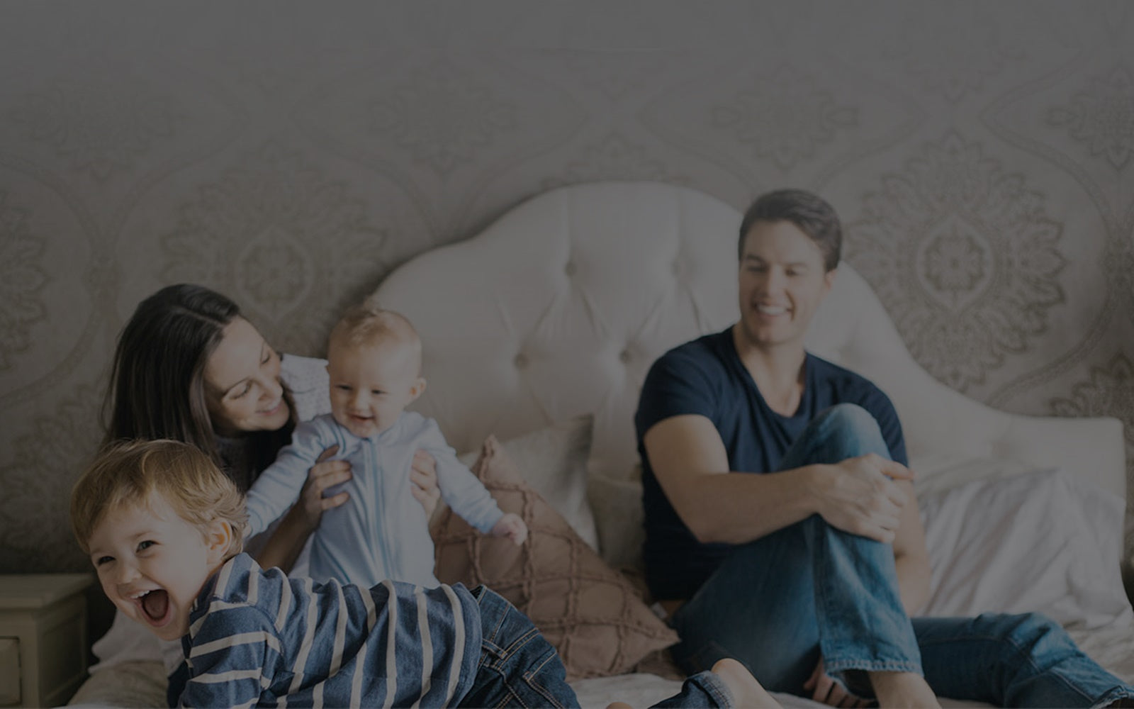 Smiling family lying in bed with a baby and toddler