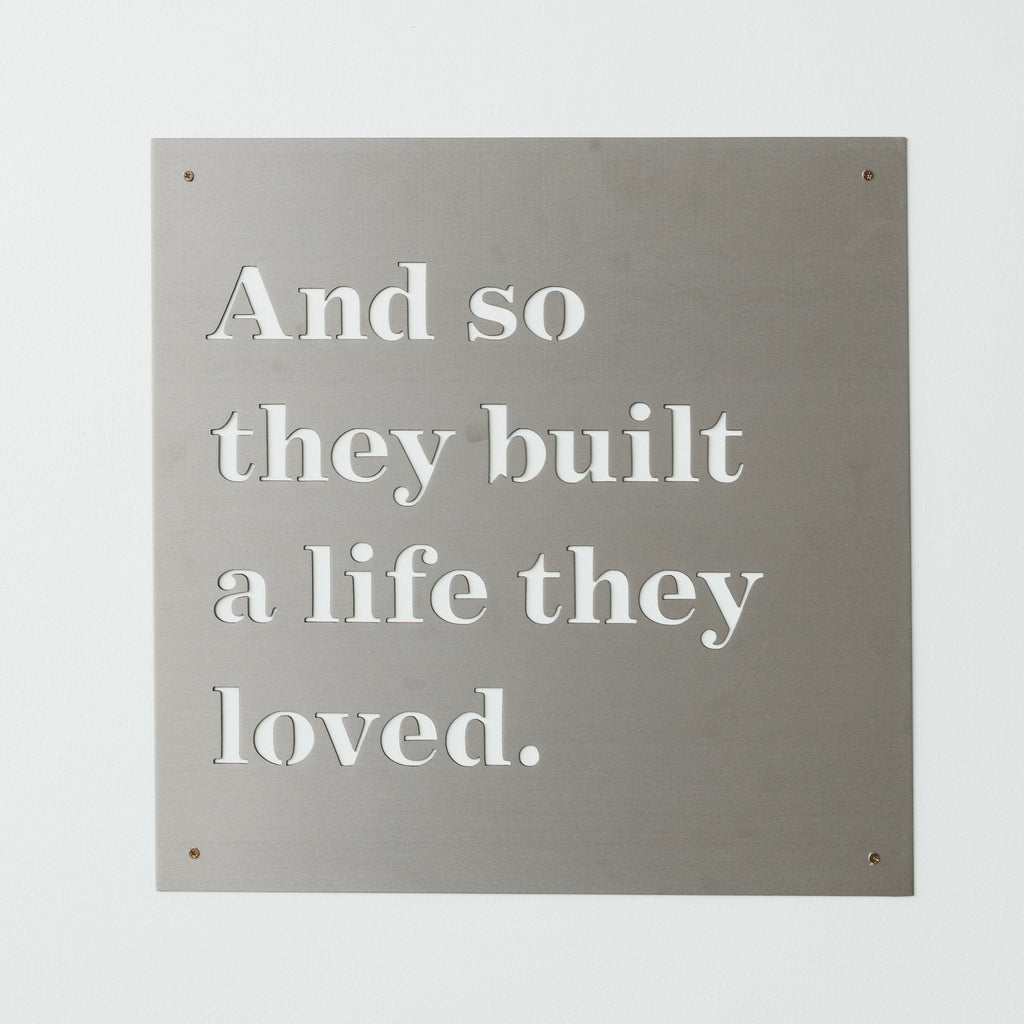 "metal quote sign that reads ""And so they built a life they loved"""