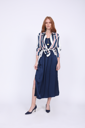Model is wearing the Hayley Tank Dress in navy with the Bold Stripe Shirt in navy, worn unbuttoned and tied at the front waist, sleeves cuffed. Also worn with blue suede, pointed toe, kitten heels.