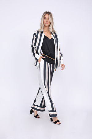 Model is wearing the Bold Stripe Shirt in black, unbuttoned, with the Hayley Camisole in black/bright white and gold chain as belt. Also worn with Bold Stripe Pant in black, and open toe, ankle strap, black high heels.