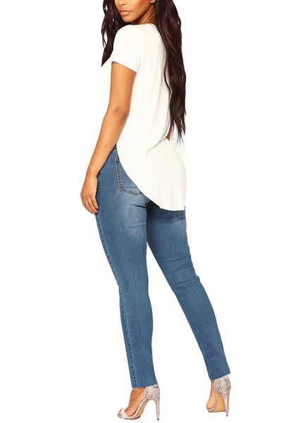 Angled full body shot of model wearing medium blue drawstring-waist washout ripped skinny jeans