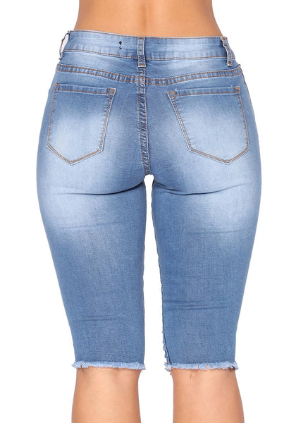 Back view of model wearing light blue knee-length raw hem distressed jeans