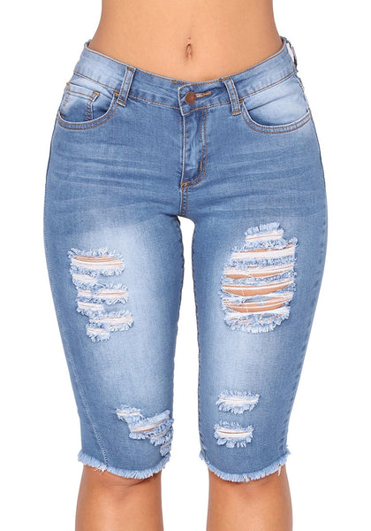 Front view of model wearing light blue knee-length raw hem distressed jeans