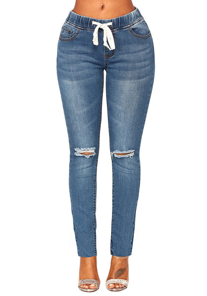 Front view of model wearing medium blue drawstring-waist washout ripped skinny jeans