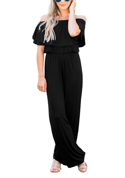 Model poses wearing black ruffled off-shoulder jumpsuit