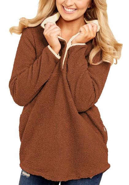 Model poses wearing dark orange button-front fleece pullover