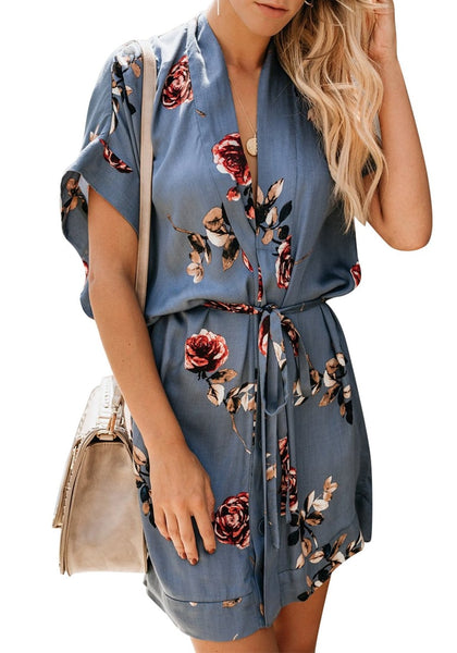 Model poses wearing light blue V-neck floral belted kimono dress