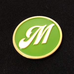 "Enamel pin - ""M"" gold - white on green"