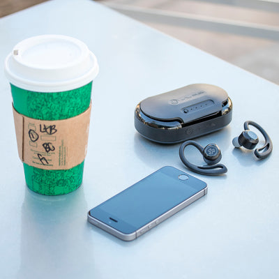Flat Lay of Black Epic Air True Wireless Earbuds and Charging Case on Table with Phone and Coffee
