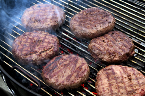 6 beef burgers cooking on a charcoal bbq