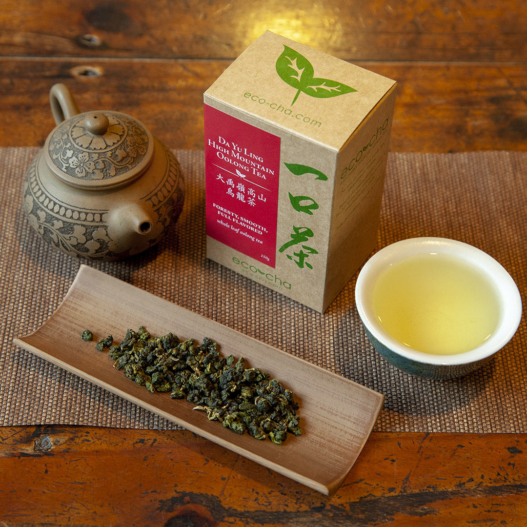 Da Yu Ling High Mountain Oolong Tea in a cup on a wooden table next to dry leaves and a box