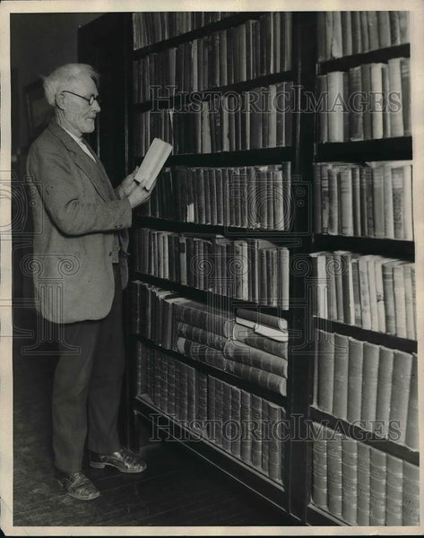 1928 Press Photo Jno Dunn, ex-convict, looking over books in the library - Historic Images