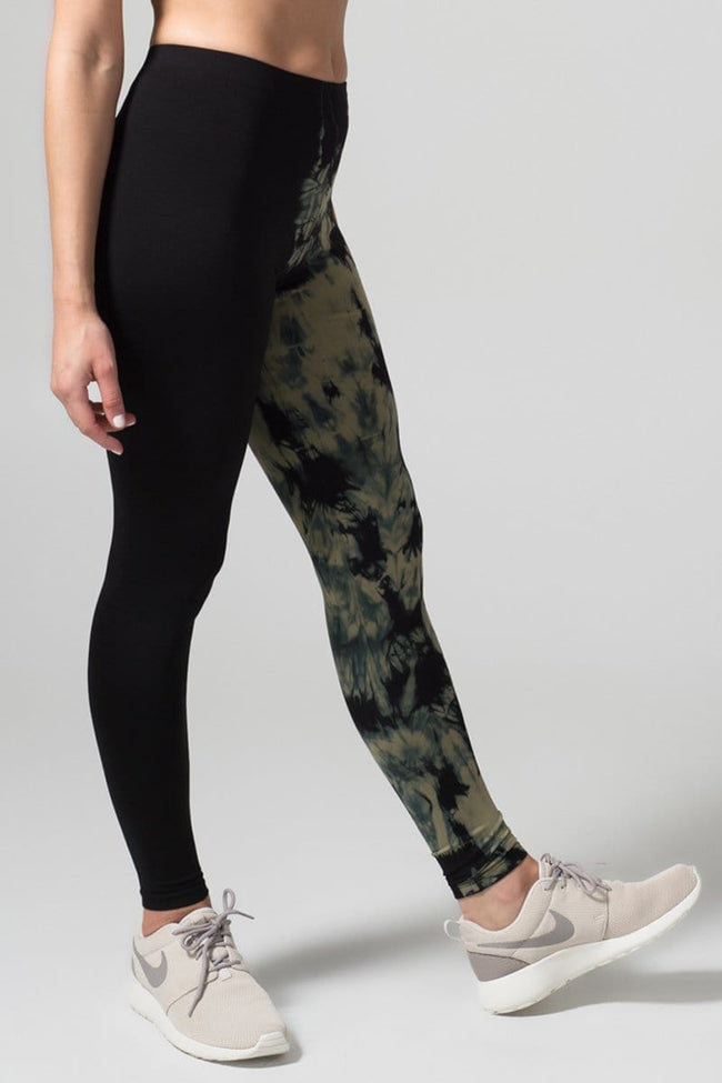 A woman with brown hair models a black sports bra, leggings, and grey sneakers. The right pant leg of the leggings is black, while the other is tie-dyed in gold and black.