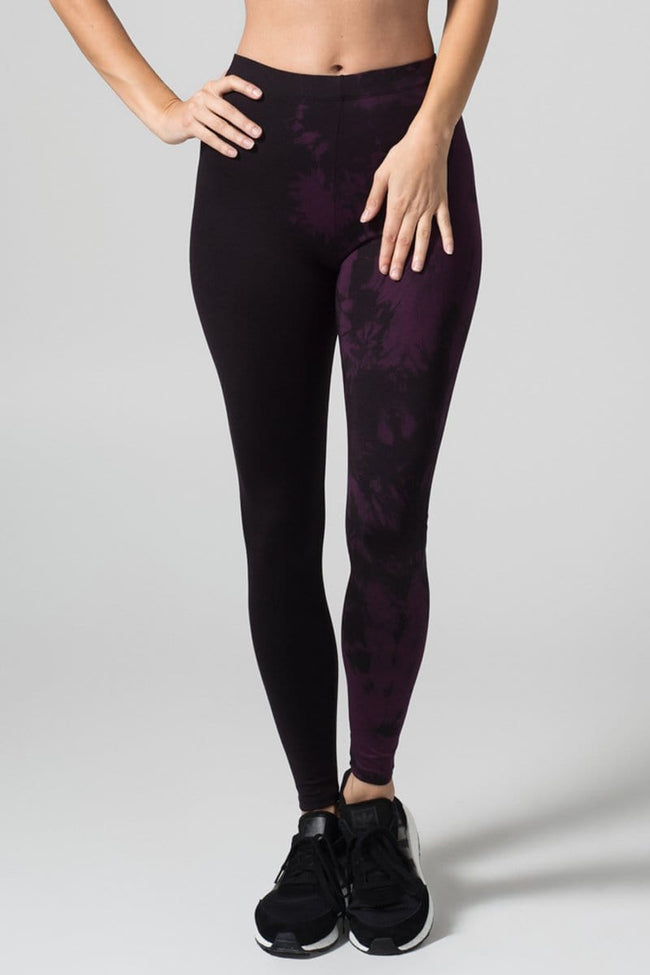 A woman with blonde hair models a black sports bra and leggings. The right pant leg of the leggings is black, while the other is tie-dyed in plum and black.