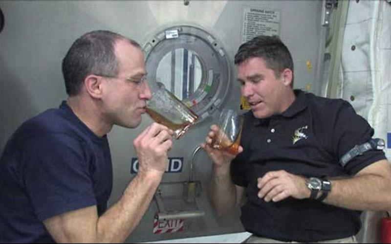 Astronaut Donald Pettit and another astronaut drink coffee in space from a zero gravity cup he designed