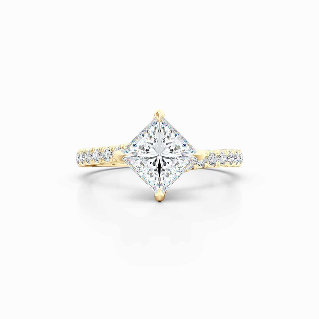 East-West, four prong, Princess Solitaire. Recessed diamond halo. Diamond adorned shoulders. Hand-fabricated in Sustainable Solid Yellow Gold. Available in Moissanite by Charles & Colvard or Lab-Grown Diamond by Diamond Foundry. | Made in Boca Raton, Florida. 15 Day Returns. Free Shipping USA. | Bashert Jewelry