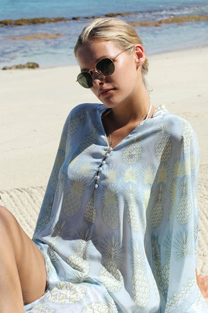 Lotty B Short Kaftan in Silk Crepe-de-Chine: PINEAPPLE - OLIVE sitting on the beach Mustique