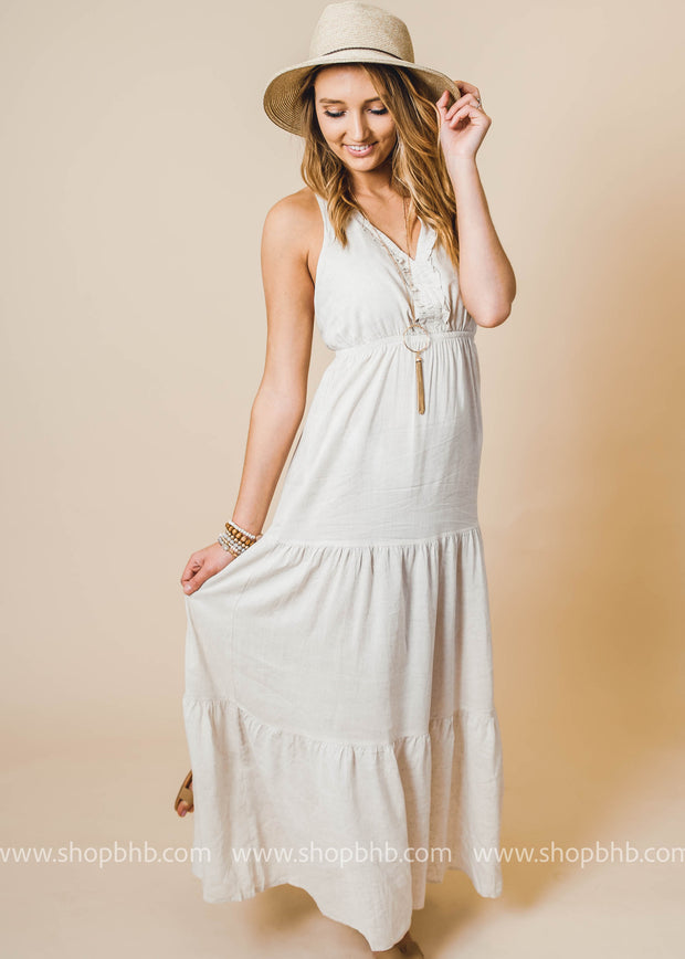 elegant white dress features  plunging neckline, sleeveless, ruffle trim, low back with X-strap, and ruffled skirt design