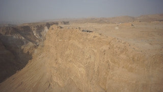 DS006B Aerial drone footage of Masada and the Dead Sea: vertical climb along Masada side with Dead Sea in background