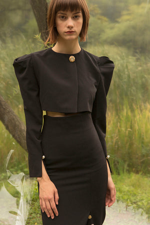 Padded shoulder with single button closure. Cropped length. Slits at cuffs.