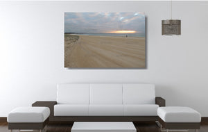 An acrylic print of a fisherman at sunrise at Blacksmiths Beach NSW hanging in a lounge room setting