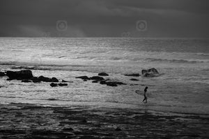 Black and white photograph of a surfer entering the water at Mollymook NSW