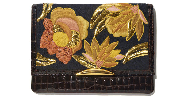 Close-up view of Port Of Call Clutch In Sunrise Flora. We can't believe we made only one of these bags -- the sumptuous detailing and rich color palette are truly to die for. One-of-a-kind chocolate patent leather fold-over clutch with textured floral embroidery, architectural gold-plated hardware and pink leather strap.