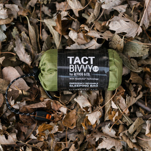 green bivy in leaves with grey sleeve
