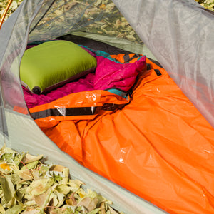 outdoor orange bivy in tent around sleeping bag