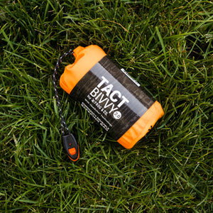 orange bivy in grass with grey sleeve