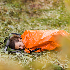 outdoor man in orange bivy on ground