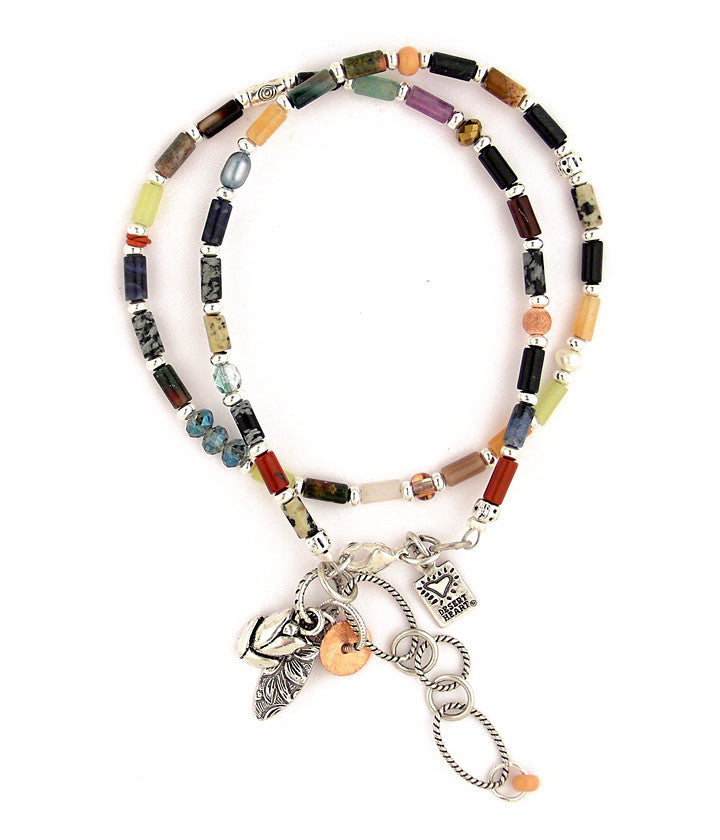 "A beautiful collection of various stone tube beads looks earthy and very Santa Fe. In between are freshwater pearls, glass and pewter. Dangling from the sterling plated and antiqued brass chain are a trio of interesting charms. 15""-17"""