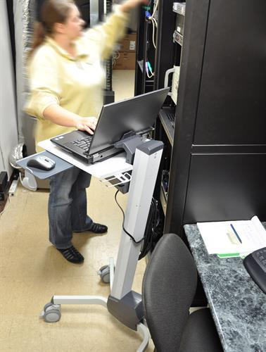Woman using mobile laptop cart while working