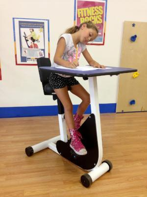 Girl using KidsFit Single Pedal Desk from Fitneff Canada in classroom