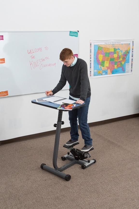 Boy using KidsFit Stepper Desk from Fitneff Canada in classroom
